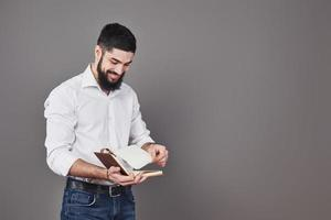 portrait of a bearded young man wearing a white shirt and holding an open planner and pulls out the page. A gray wall background photo