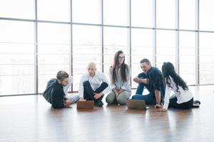 Young creative people in modern office. Group of young business people are working together with laptop. Freelancers sitting on the floor. Cooperation corporate achievement. Teamwork concept photo