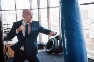 An angry bald businessman beats a boxing pear in the gym. concept of anger management photo