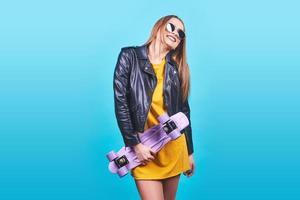 atractiva chica bronceada con sonrisa en la cara viste chaqueta de cuero negro posando con placer. Fotografía interior de una mujer encantadora en gafas de sol de pie con patineta sobre fondo azul. foto