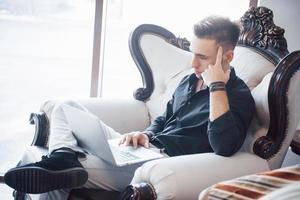 joven empresario trabajando en oficina loft moderno. hombre vestido con camisa blanca y usando una computadora portátil contemporánea. Fondo de ventanas panorámicas. foto