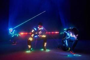 Laser show performance, dancers in led suits with LED lamp, very beautiful night club performance, party photo