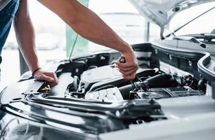 Aquí vamos. proceso de reparación de coche tras accidente. hombre trabajando con motor debajo del capó foto