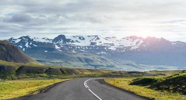 Travel to Iceland. road in a bright sunny mountain landscape. Vatna volcano covered with snow and ice on tne background photo