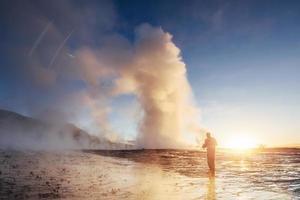 erupción del géiser strokkur en islandia. colores fríos de invierno, el sol se ilumina a través del vapor foto