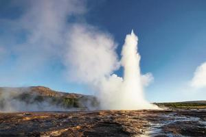 Strokkur geyser eruption in Iceland. Fantastic colors shine through the steam. Beautiful pink clouds in a blue sky photo