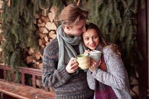 pareja joven desayunando en una cabaña romántica al aire libre en invierno. vacaciones de invierno y vacaciones. Pareja de Navidad de hombre y mujer felices beben vino caliente. pareja enamorada foto