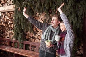 foto de hombre feliz y mujer bonita con tazas al aire libre en invierno. vacaciones de invierno y vacaciones. Pareja de Navidad de hombre y mujer felices beben café caliente. hola vecinos