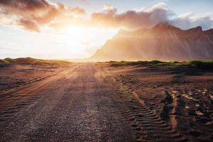 Fantastic sunset of the mountains and volcanic lava sand dunes to the beach in Stokksness. the concept of a hot day and a desert photo