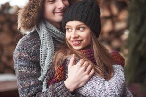 cintura para arriba retrato de un joven despreocupado y una mujer abrazándose y sonriendo. Están parados en el bosque de invierno y mirando a la cámara con felicidad. foto