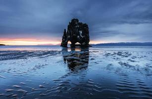 Hvitserkur is a spectacular rock in the sea on the Northern coast of Iceland. Legends say it is a petrified troll. On this photo Hvitserkur reflects in the sea water after the midnight sunset