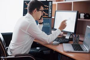 Stockbroker in shirt is working in a monitoring room with display screens. Stock Exchange Trading Forex Finance Graphic Concept. Businessmen trading stocks online photo
