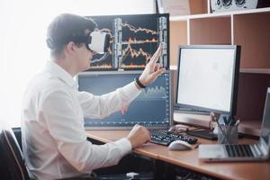 Businessman in virtual reality trading on stock market. Multiple computer screens ful of charts and data analyses in background photo
