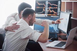 equipo de corredores de bolsa está conversando en una oficina oscura con pantallas de visualización. analizar datos, gráficos e informes con fines de inversión. comerciantes creativos de trabajo en equipo foto