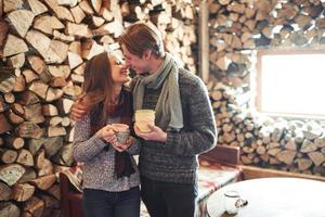 foto de hombre feliz y mujer bonita con tazas al aire libre en invierno. vacaciones de invierno y vacaciones. Pareja de Navidad de hombre y mujer felices beben vino caliente. pareja enamorada