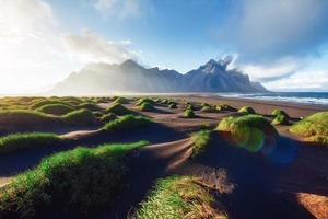 Fantastic west of the mountains and volcanic lava sand dunes on the beach Stokksness, Iceland. Colorful summer morning Iceland, Europe photo