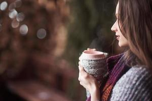 oman wearing warm knit clothes drinking cup of hot tea or coffee outdoors photo