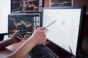 Analyzing data. Close-up of young businessman pointing on the data presented in the chart with pen while working in creative office photo
