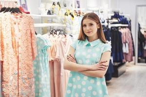 Woman shopping clothes. Shopper looking at clothing indoors in store. Beautiful happy smiling asian caucasian female model photo