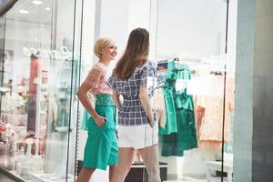 Shopping therapy in action. Rear view of two beautiful women with shopping bags looking at each other with smile while walking at the clothing store photo