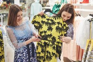 Hermosas mujeres jóvenes en el mercado semanal de telas: mejores amigas compartiendo tiempo libre divirtiéndose y comprando foto
