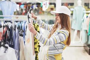 concepto de venta, moda, consumismo y personas - mujer joven feliz con bolsas de compras eligiendo ropa en el centro comercial o tienda de ropa foto