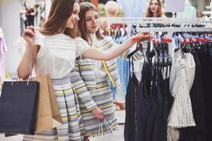 gran día para ir de compras. Dos hermosas mujeres con bolsas de la compra mirando el uno al otro con una sonrisa mientras camina en la tienda de ropa foto