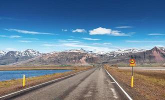 camino en las montañas. Puente sobre un canal que conecta la laguna jokulsarlon y el océano atlántico en el sur de Islandia foto