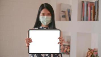 mujer asiática con una máscara que sostiene una tableta frente a la pantalla frontal para recibir un mensaje de protección contra el virus corona o covid-19. foto