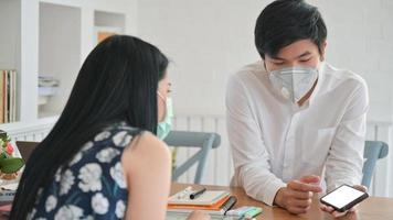 Las mujeres asiáticas y los hombres jóvenes que usan una máscara están discutiendo su trabajo en casa para proteger al covid-19. foto