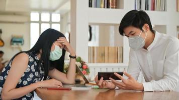 los hombres y las mujeres usan máscaras para protegerse del virus. se están reuniendo a través de la aplicación con el teléfono inteligente. foto
