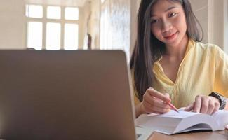 Asian teenage female student search for information from laptop and take notes. She prepares for university entrance exam. photo