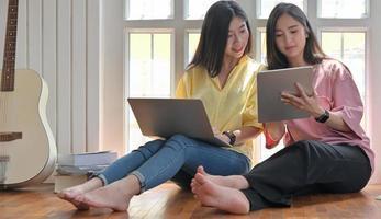dos mujeres asiáticas utilizan la computadora portátil durante su tiempo libre en casa durante el brote del virus. foto