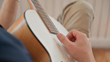 Primer plano de un joven tocando la guitarra en su casa que se detuvo en su casa debido al brote del virus. foto