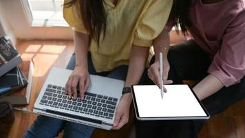 dos estudiantes universitarias usan una tableta y una computadora portátil para estudiar en línea en casa para prevenir el brote del virus covid-19. foto