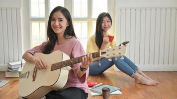 Asian teenage girls are singing and playing guitars.They stay at home to prevent the corona virus outbreak. photo