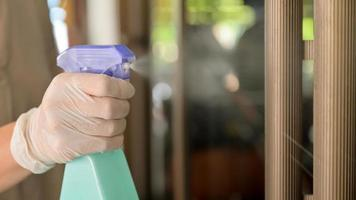 Close-up shot of Spray cleaning agent on the door handles to prevent disease. photo