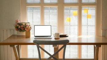 Cropped shot of classic workplace with a laptop, coffee cup and stationary on a wooden table near the window. photo