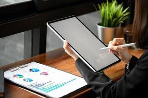 Toma recortada de una empleada que usa un lápiz para escribir en una tableta y gráficos de documentos sobre la mesa. foto