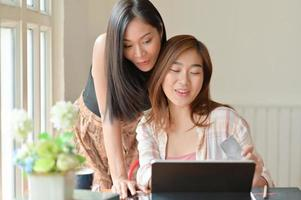 Two Asian women hold a credit card and use a laptop to search for shopping information. photo
