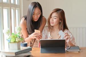 Two Asian women hold a credit card and use a smartphone to search for shopping information. photo