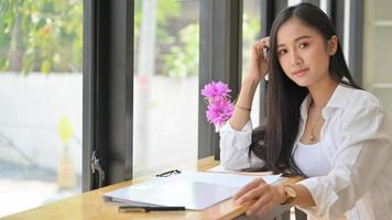 estudiante asiática con materiales de estudio en un espacio de trabajo compartido, ella mirando a la cámara y sonriendo. foto
