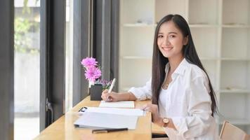Asian woman wearing a white dress holding a pen to write notes in a comfortable office. She looked at the camera and smiled. photo