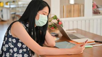 Woman wearing a mask is using a smartphone in a cafe.She is at risk of being infected with the Covid-19 virus. photo