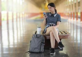 Female traveler looking at smartphone while waiting for a train on platform. photo