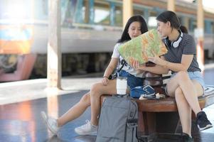 A young female traveler is looking at a map on the train platform. photo