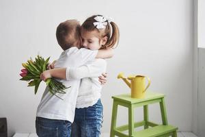 hermoso niño y niña con tulipanes con abrazo. día de la madre, 8 de marzo, feliz cumpleaños foto