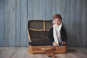 Happy kid in pilot hat playing with old suitcase. Childhood. Fantasy, imagination. Holiday photo