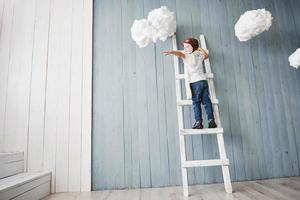 Little boy in pilot hat standing on the ladder in the studio. Reach to heaven. Touch the clouds concept photo