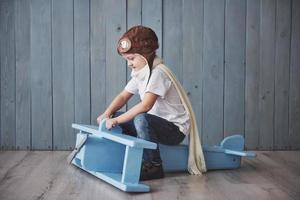 Happy kid in pilot hat playing with wooden airplane against. Childhood. Fantasy, imagination. Holiday photo